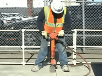 Figure 2: Worker using jackhammer with Lift Assist. (Note: Lift Assist is the black cylinder