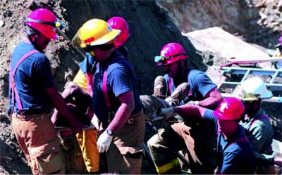 A fire department rescue team helps a worker to safety after a trench cave-in.