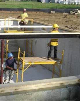 Figure 18 - Workers installing a steel beam from a mobile scaffold.