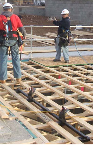 Figure 20 - Workers using a truss bracket anchor while installing a subfloor.