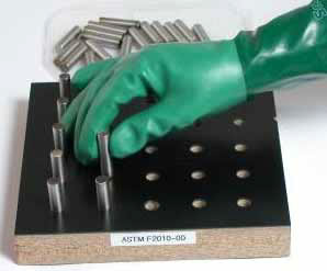 photo of a dexterit test where a gloved hand has to pick up metal plugs