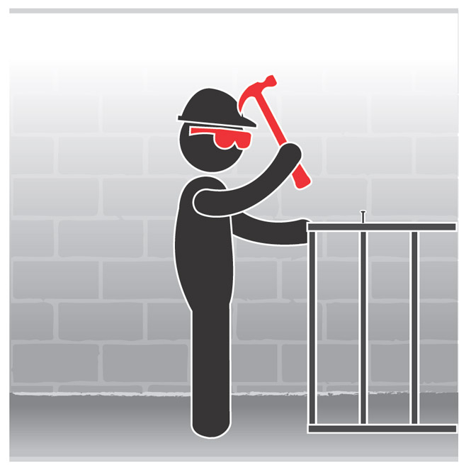 Graphic of a worker wearing eye protection and hammering a nail.