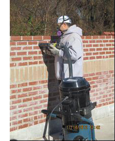 image of construction worker tuckpointing a brick wall