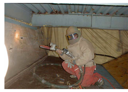 Photo of worker using abrasive blasting on a wall.