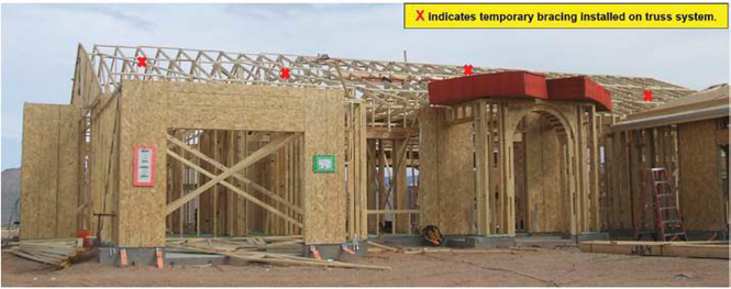 Photo 1: House in frame just after trusses erected and set. Stack of OSB above entryway to the right was being put into position when worker fell.
