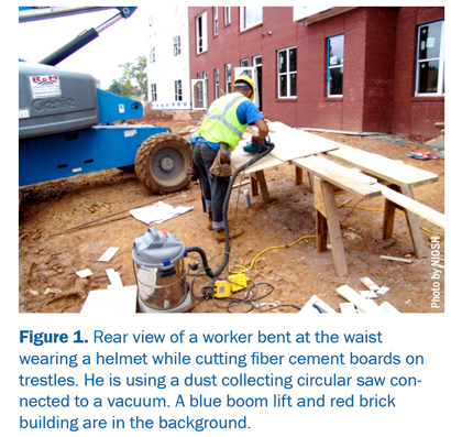 Figure 1: Rear view of a worker bent at the waist wearing a helmet while cutting fiber cement boards on trestles. He is using a dust collecting circular saw con¬nected to a vacuum. A blue boom lift and red brick building are in the background.