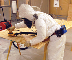 Photo of a worker with full protective gear conducting CPWR test inside a special chamber using a dust collection system