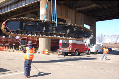 Two men guiding a lifted conveyor belt. Photo courtesy International Union of Operating Engineers and Neil W. Lippy.