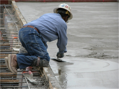 Man in an awkward position, kneeling and smoothing concrete. Photo courtesy CPWR's electronic Library of Construction Safety and Health (eLCOSH).