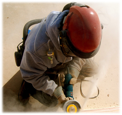 Photo of a worker using a saw while wearing protective clothing for the dust