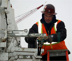 Photo of a man working while it is snowing.