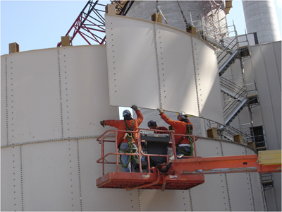 Men on a lift putting a panel into place. Photo courtesy of International Brotherhood of Boilermakers.