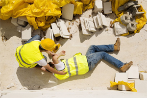 Photo of a construciton worker lying on the ground with another aiding him.