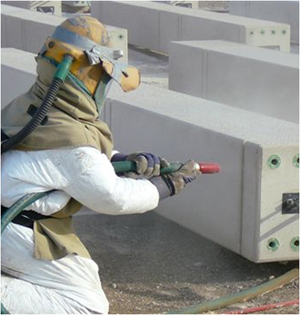 Fully protected person with PPE equipped with helmet, air filtration gloves, coveralls, apron, while abrasive blasting