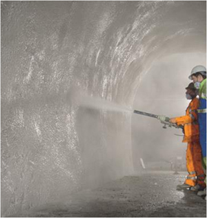 shotcrete being applied by workment covered with PPE