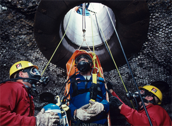 Men extracting a worker from a confined space, all with respirators on