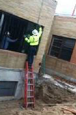 Worker using a stepladder improperly by standing on its top