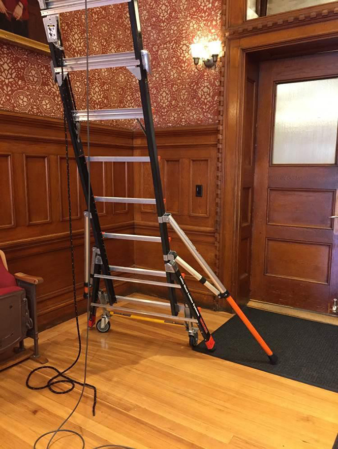 photo of platform ladder with one wheel lift assembly engaged and one outrigger deployed